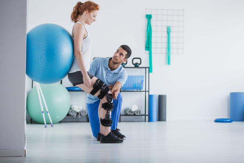 Kontuzja sportowca - młoda kobieta podczas rehabilitacji po kontuzji kolana.