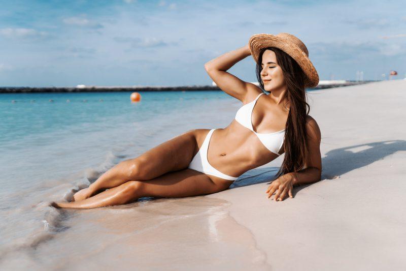 Bikini body - młoda kobieta w bikini leżąca na plaży.